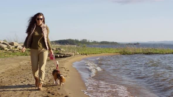 Thumbnail for Young Woman Enjoying Walk with Dog along Lake Shoreline
