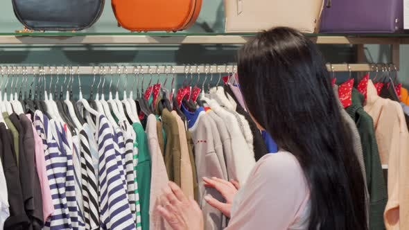 Thumbnail for Young Woman Examining Clothes on Sale at the Fashion Store