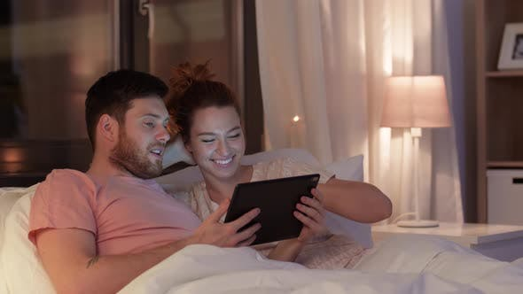 Thumbnail for Happy Couple Using Tablet Computer in Bed at Night