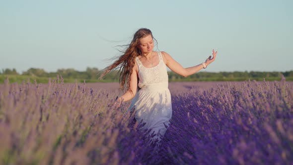 Young Girl Walks Among Lavender in the Daytime