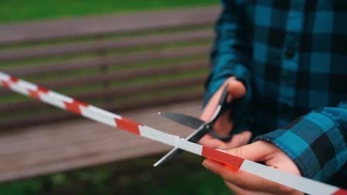 Schneiden Sie das Cordon Tape-Band mit einer Schere. Ende der Mobilitätseinschränkungen Coronavirus. Schere