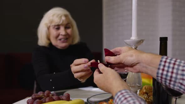 Thumbnail for Senior Woman Being Surprised By Marriage Proposal with Engagement Ring of Her Grandfather Husband