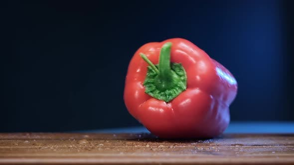 Red Bell Pepper Falls on Brown Wooden Board in Restaurant