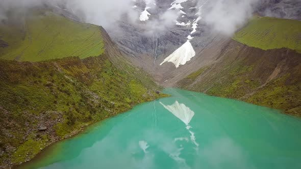 Aerial view of cloudy, snowy Humantay Lake, Peru.