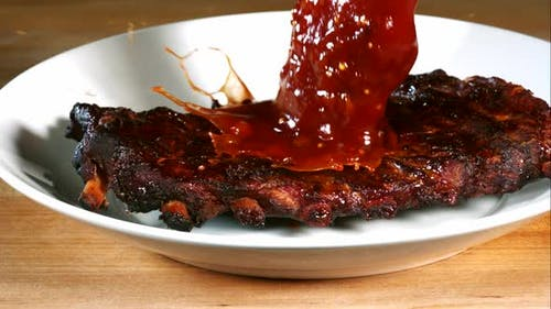 BBQ sauce pouring and splashing in ultra slow motion