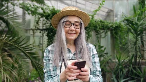Senior Woman in Hat which Using Smartphone in Beautiful Orangery