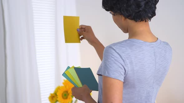 Thumbnail for Black woman using paint chips to pick out color for room