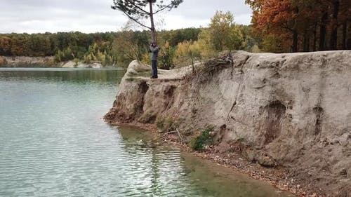 Man taking photo of landscape. Aerial view of man photographer taking photo on lake shore