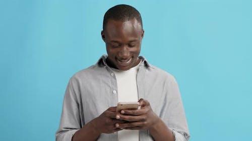 Happy African American Guy Texting on Cellphone