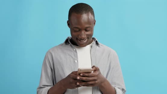 Thumbnail for Happy African American Guy Texting on Cellphone