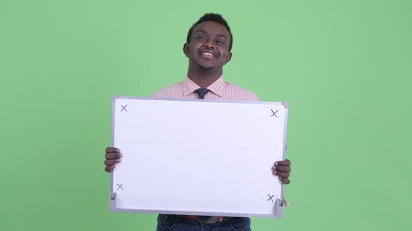 Thumbnail for Happy Young African Businessman Thinking While Holding White Board