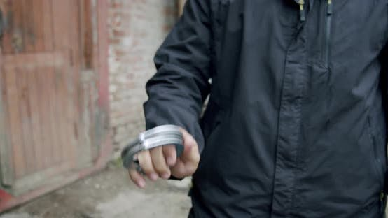 Thumbnail for the Policeman Pulls Out the Handcuffs and Holds Them in Front of Him Close Up.