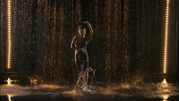 Silhouette of an Attractive Woman in a Wet Tight Dress Enjoying a Flamenco Dance in the Rain. Black