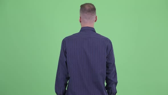 Cover Image for Rear View of Businessman Thinking and Looking Around