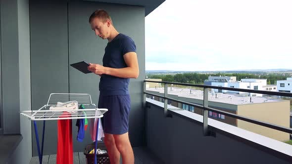 Thumbnail for A Young Man Takes Down Clothes From the Drying Rack on the Balcony and Works on the Tablet