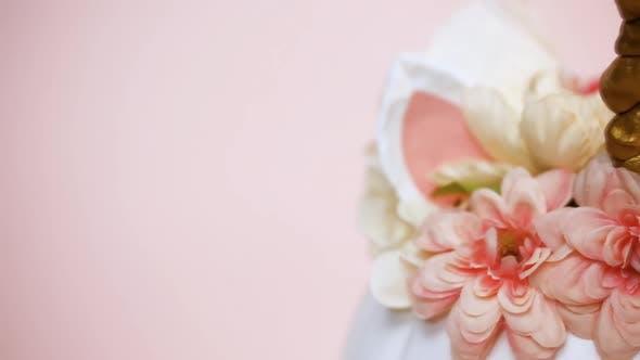 Thumbnail for Nahansicht. Craft Kürbis bemalt weiß und verziert mit rosa Blumen als Einhorn auf rosa Backgr