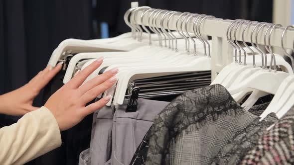 Closeup of Female Hands Plucked a Hanger with Clothes