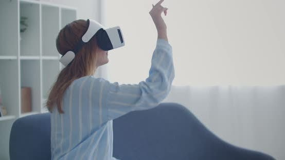 Young Girl in Virtual Reality Headset Scrolling in Air at Home Technology Concept.