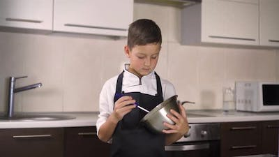 The Little Boy in a Suit of the Cook. Baby Make Dinner in Chef Suit