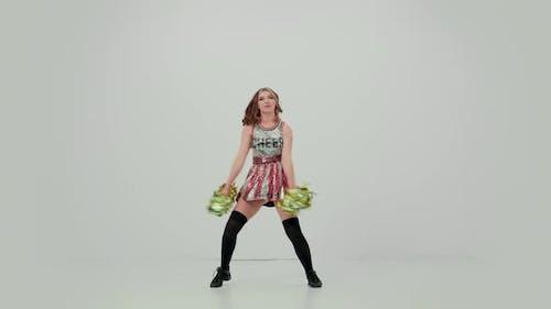 Charmante Cheerleaderin in Uniform mit Pompoms tanzt einen jubellichen Tanz im Studio auf einem Weißen