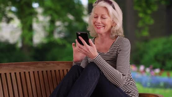Thumbnail for Happy older woman text messaging with smartphone while sitting on park bench
