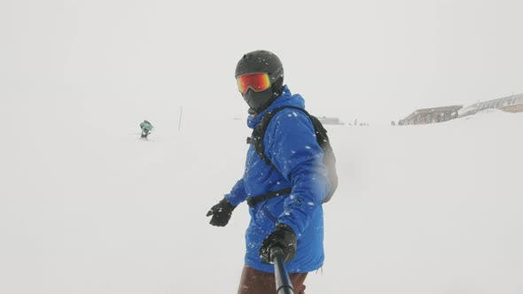 Snowboarder on Snowboard Running Down the Slope in Ski Resort