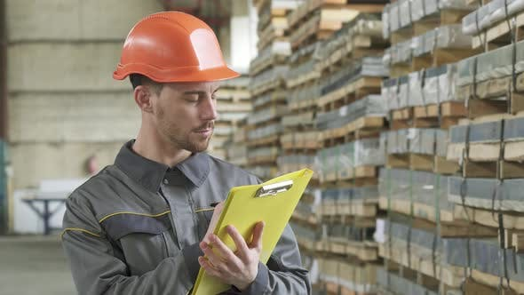 Thumbnail for Warehouse Worker Writing on His Clipboard Standing at the Storage