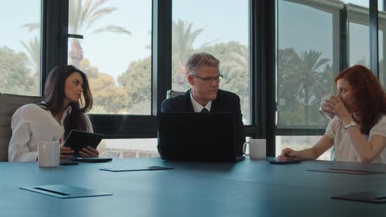 Group of three business people meeting in an office to work on a project. Slow motion