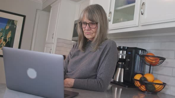 Low angle view of Senior white woman typing email on laptop computer in kitchen