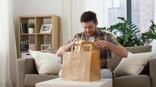 Thumbnail for Smiling Man Unpacking Takeaway Food at Home