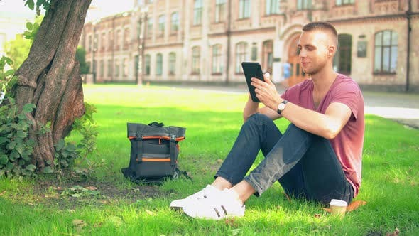 Thumbnail for Young Man Sits Near the Tree Use Gadget
