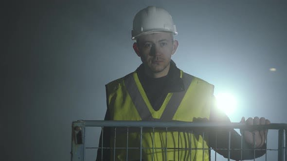 Thumbnail for Serious Man in the Builders Uniform and Helmet Standing in Front of the Black Background with