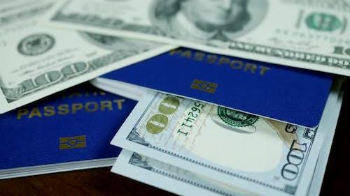 Dollar Bills and Blue ID Passports on Wooden Background