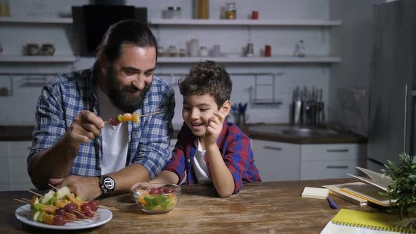 Thumbnail for Father and Son Preparing Fruit Skewers in Kitchen