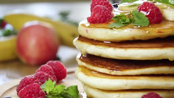 Pouring Honey on Stack of Pancakes