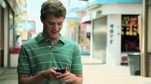Teenage boy using cellphone and laughing