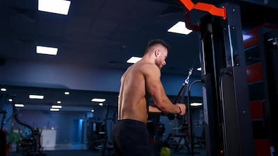 Fit muscular man is exercising with sport equipment.