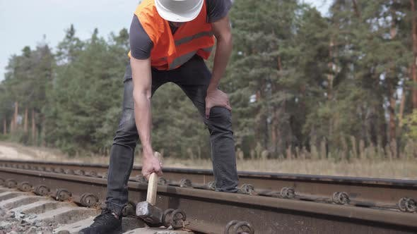 A Railway Man in a Helmet Repairs a Railway, Hammering the Spire with a Sledgehammer