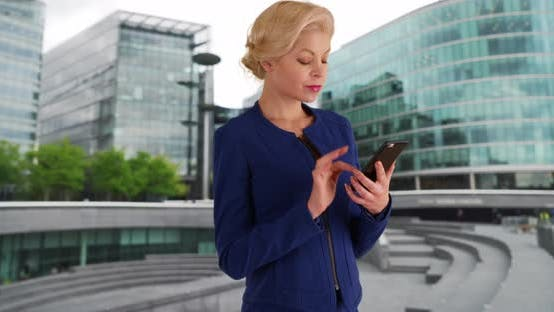 Successful female executive replying to message with mobile