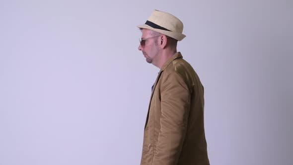 Thumbnail for Rear View of Blonde Casual Businessman with Hat and Sunglasses Looking Back