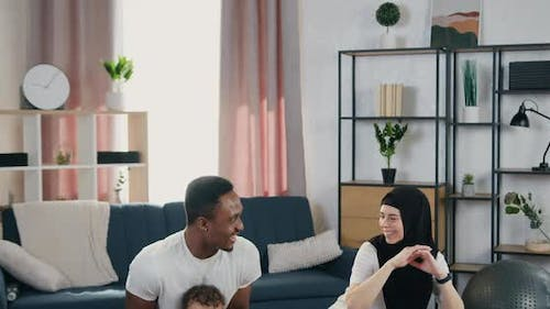 Multiethnic Couple with Small Son which Squating Together During Home Training
