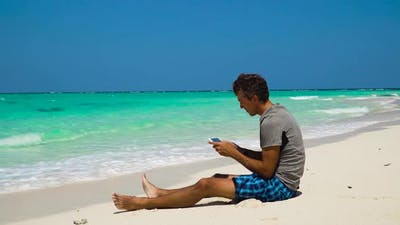 Man with Cellphone on the Tropical Beach