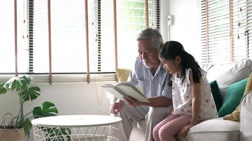 Senior man teaching girl to read book