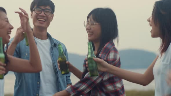 Group of Asia best friends dancing and drinking have fun salute toast of bottle beer enjoy party.