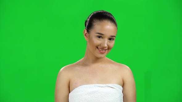 Thumbnail for Attractive Woman in White Towel Smiles Coquettishly and Winks Looking at the Camera, Green Screen