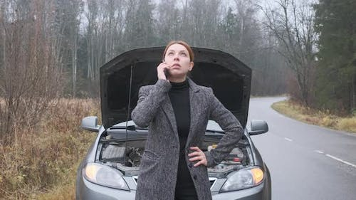 Young Woman Calling Car Assistance Services Standing By Breakdown Automobile on the Roadside