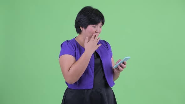 Thumbnail for Happy Young Overweight Asian Woman Using Phone and Looking Surprised