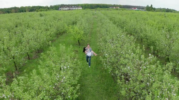 Cover Image for Drone View of Groom Carrying Beloved Bride in Arms