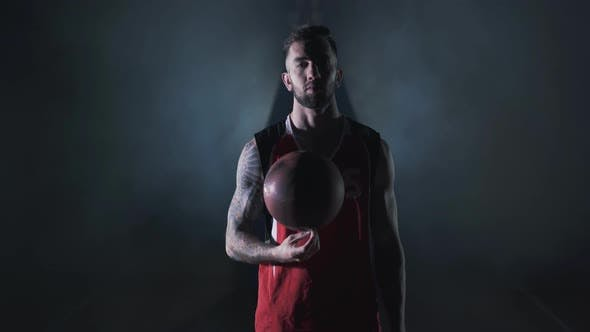 Thumbnail for Portrait Young Handsome Bearded Brutal Confident Basketball Player Stand with a Ball in the Clouds