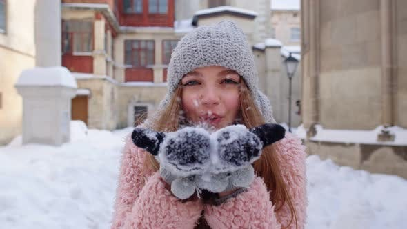 Young Woman Traveler Tourist Showing Snow in Hands Palms To Camera and Blowing It on City Street